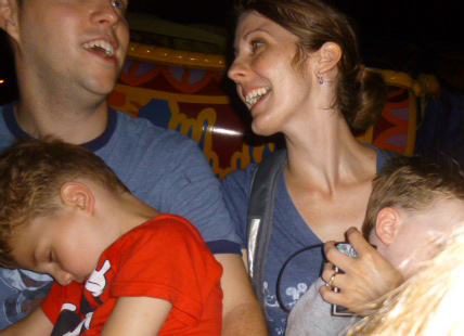 """My sister snapped this pic behind her back of my husband and I singing """"A Whole New World"""" on The Magic Carpets of Aladdin, while holding our sleeping kids.  We couldn't decide if we were great parents for having our kids at Disney World or bad ones for carting them around so we could keep having fun!"""